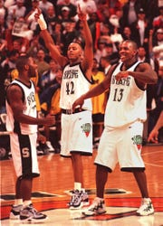 MSU's Mateen Cleaves, left, Morris Peterson, center, and Antonio Smith celebrate the team's victory against Michigan Tuesday night.