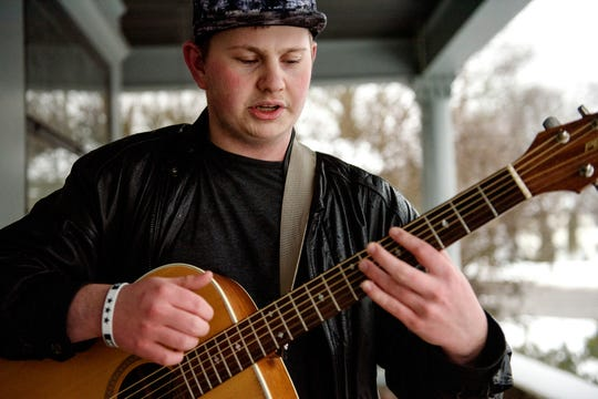 Garrett Blocker, 18, sings an original song on the front porch of his home after taking his dog Jake for a walk after work on Wednesday, Feb. 20, 2019, in Charlotte.