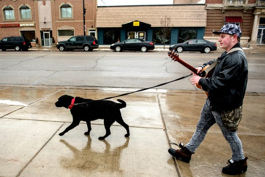 Garrett Blocker, 18, sings while taking his dog Jake for a walk after work on Wednesday, Feb. 20, 2019, in downtown Charlotte. Blocker has autism and says singing helps him cope and express himself in a world where social interaction is hard for him. Blocker's sidewalk performances are sometimes caught on video and shared on social media.