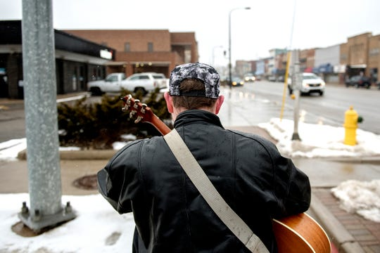 Garrett Blocker, 18, sings while walking his dog Jake after work on Wednesday, Feb. 20, 2019, in downtown Charlotte. Blocker has autism and says singing helps him cope and express himself in a world where social interaction is hard for him. Blocker's sidewalk performances are sometimes caught on video and shared on social media.