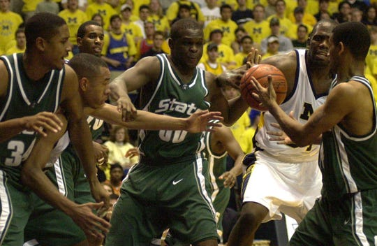 Andre Hutson, Zach Randolph and Charlie Bell fight inside for a rebound during second half action against Michigan.