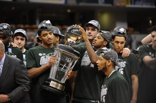 MSU players celebrate with the trophy after defeating Michigan in the Big Ten Championship title game on March 16, 2014.