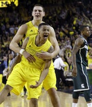 Michigan guard Trey Burke and forward Mitch McGary celebrate their 58-57 win over Michigan State on March 3, 2013.