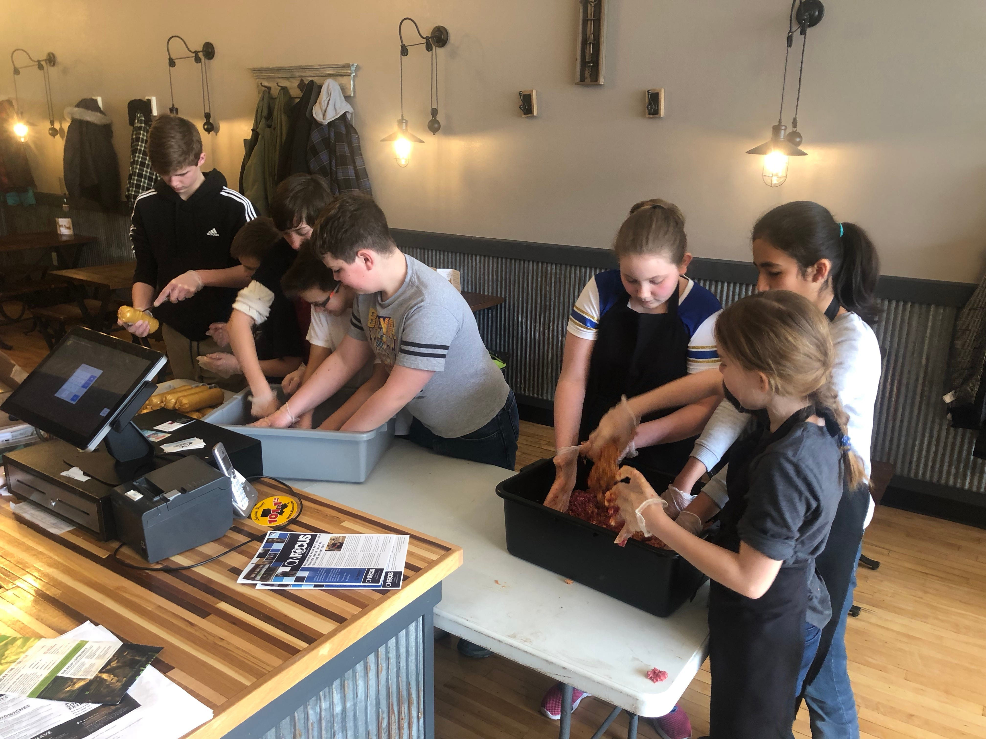 Boys and girls who are members of Marshfield Scouts BSA Troops 392 worked together to prepare a dinner of spaghetti and meatballs for police officers at MoJo's.