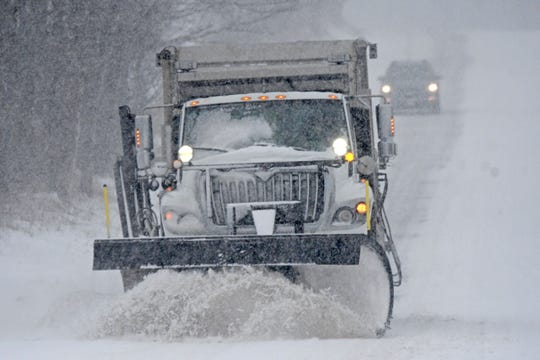 An Ohio Department of Transportation snow plow driver clears a section of Ohio 96 on Wednesday as a following motorist enjoys the cleared path.