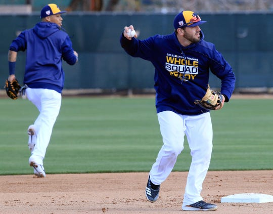 Milwaukee Brewers infielder Orlando Arcia, watches as Mike Moustakas completes a double play, during spring training drills on Tuesday.