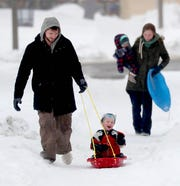 Josh Krecioch of Waukesha pulls his 2-year-old son Kai on a sled as his wife, Hailey, walks behind with their 1-year- old daughter Zahlia down East Lafayette Place after sledding nearby at Lafayette Hill Road in Milwaukee on Wednesday, Feb. 20, 2019. Another round of snow fell Wednesday morning.