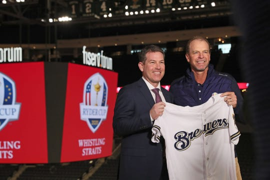 Steve Stricker (right) gets presented with a Milwaukee Brewers jersey by Milwaukee Brewers TV announcer Brian Anderson after being introduced as the U.S. captain for the 2020 Ryder Cup.