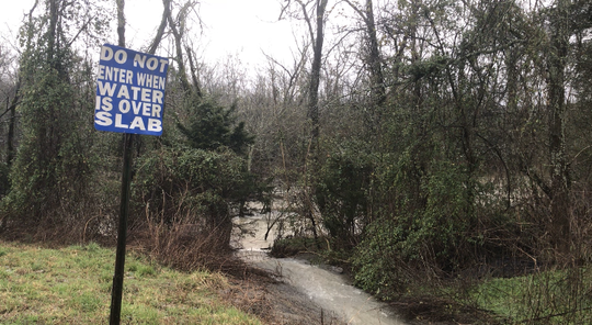 A sign near Cripple Creek in Readyville, Tenn. warns drivers to be weary of the flooded roadway on Wednesday, Feb. 29, 2019.