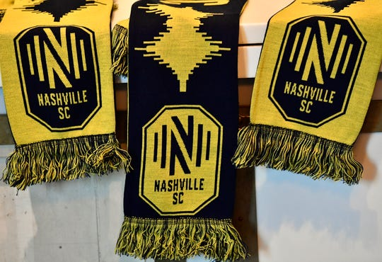 Scarves rest on a shelf with the Nashville MLS franchise new logo and team name at Marathon Music Works Wednesday, Feb. 20, 2019 in Nashville, Tenn.