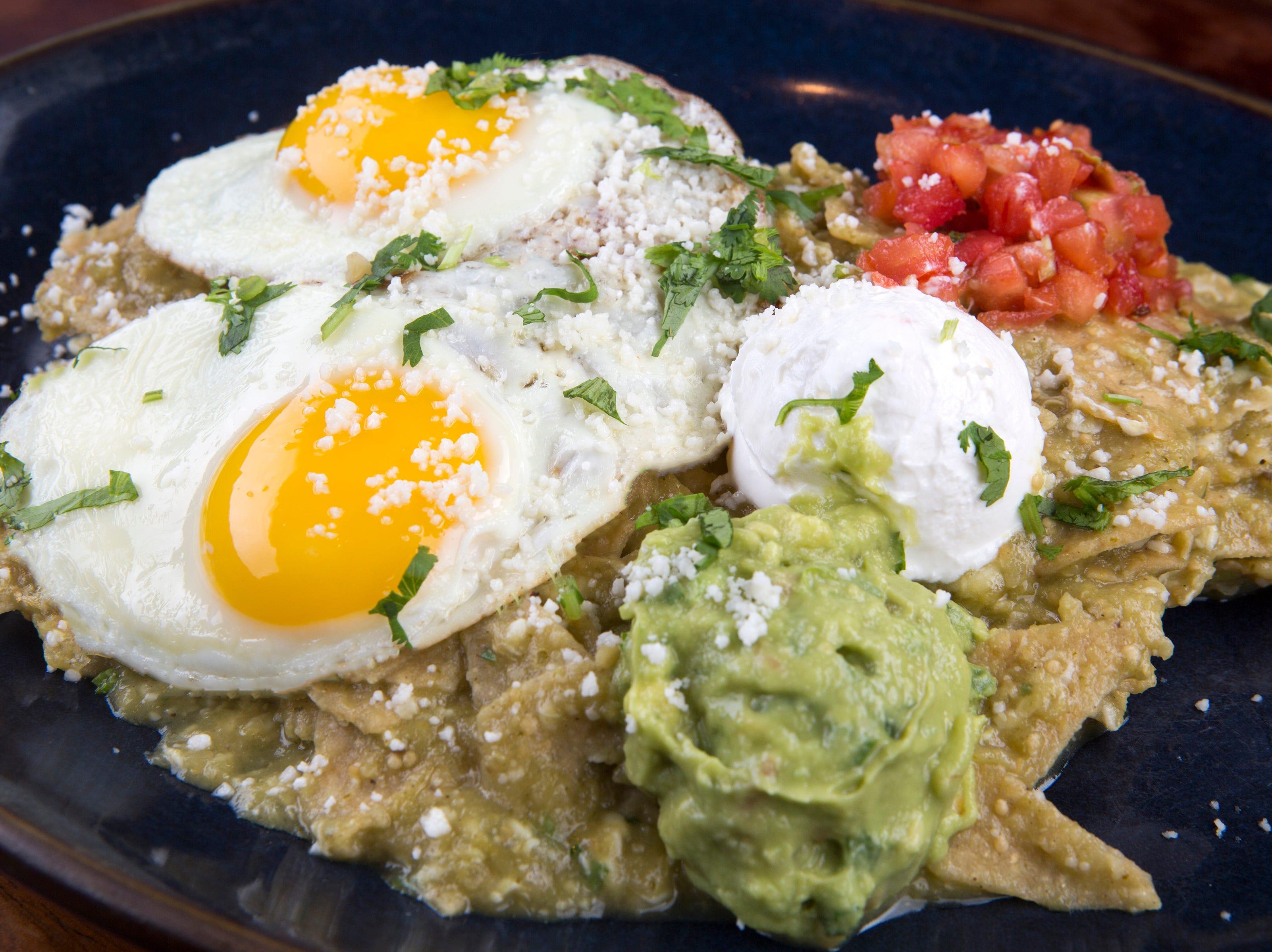 Huevos Rancheros Divorciados for brunch at Rocco's Tacos features sunny-side-up eggs on tostadas, refried beans, salsa roja, salsa verde, cotija cheese, pico de gallo, sour cream and guacamole.