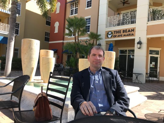 Dr. Beau Braden, founder of Braden Clinic, who plans to build a 25-bed hospital in Ave Maria, enjoys coffee in the town center recently.