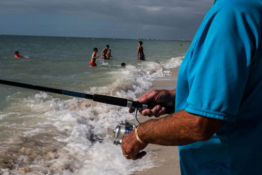 Ronald Levinsohn fishes while children play on the shoreline at Bonita Beach on Wednesday, Feb. 20, 2019. Levinsohn traveled from Cleveland to vacation in the area.