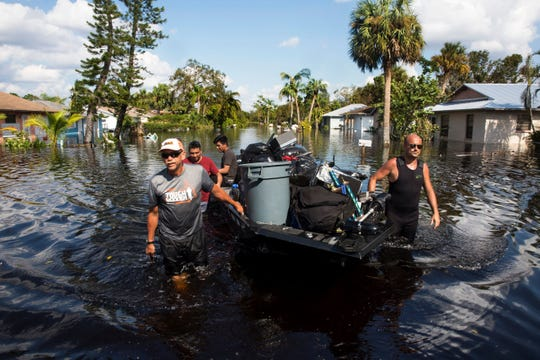 Don Manley, left, and Pedro Castellano pull Manley's boat, loaded with residents' belongings, along flooded Chapman Avenue in Bonita Springs on Friday, Sept. 15, 2017, five days after Hurricane Irma.