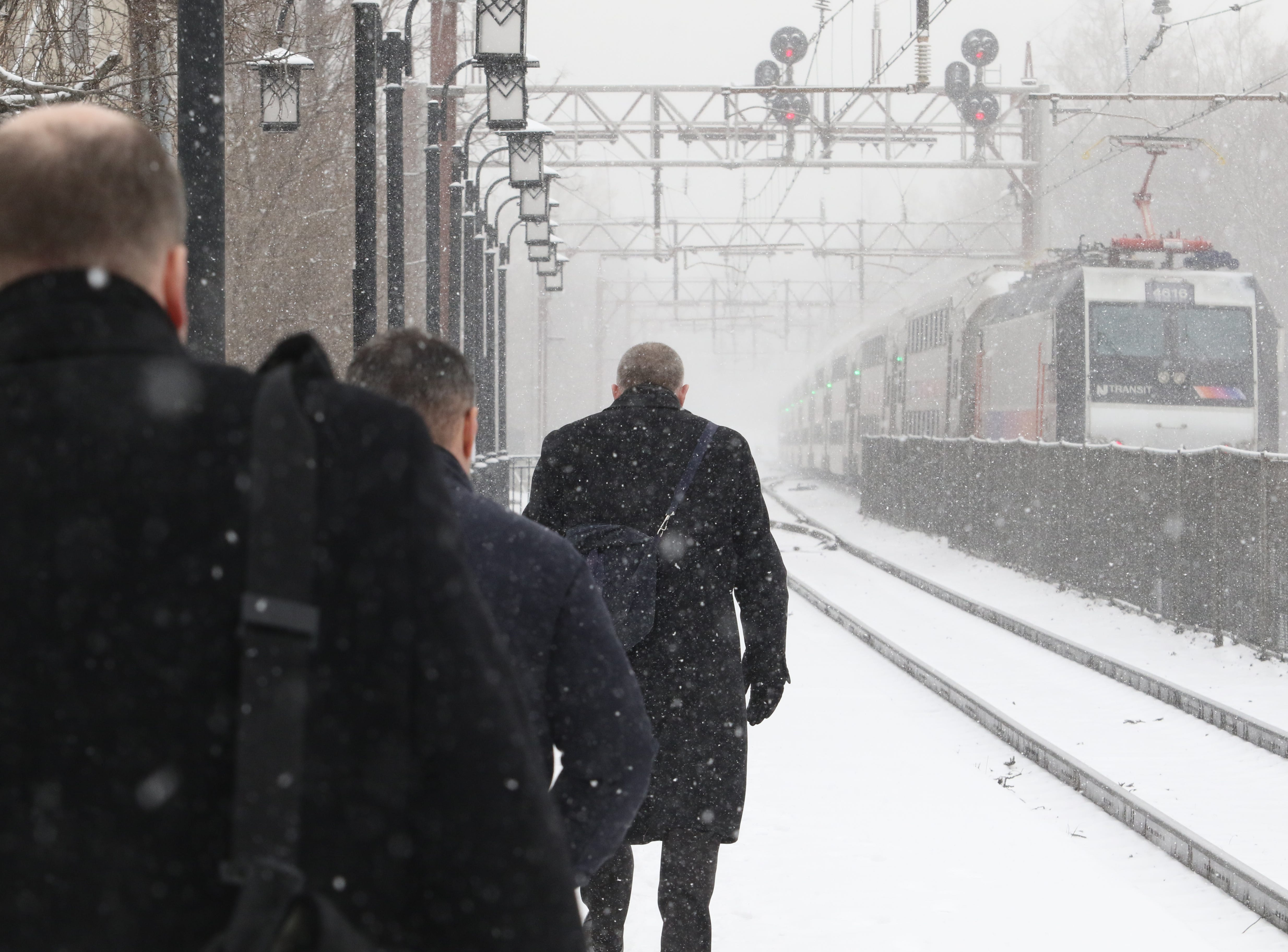 Afternoon commuters depart the train that pulled into the Morristown Train Station in heavy snow this afternoon on February 20, 2018.