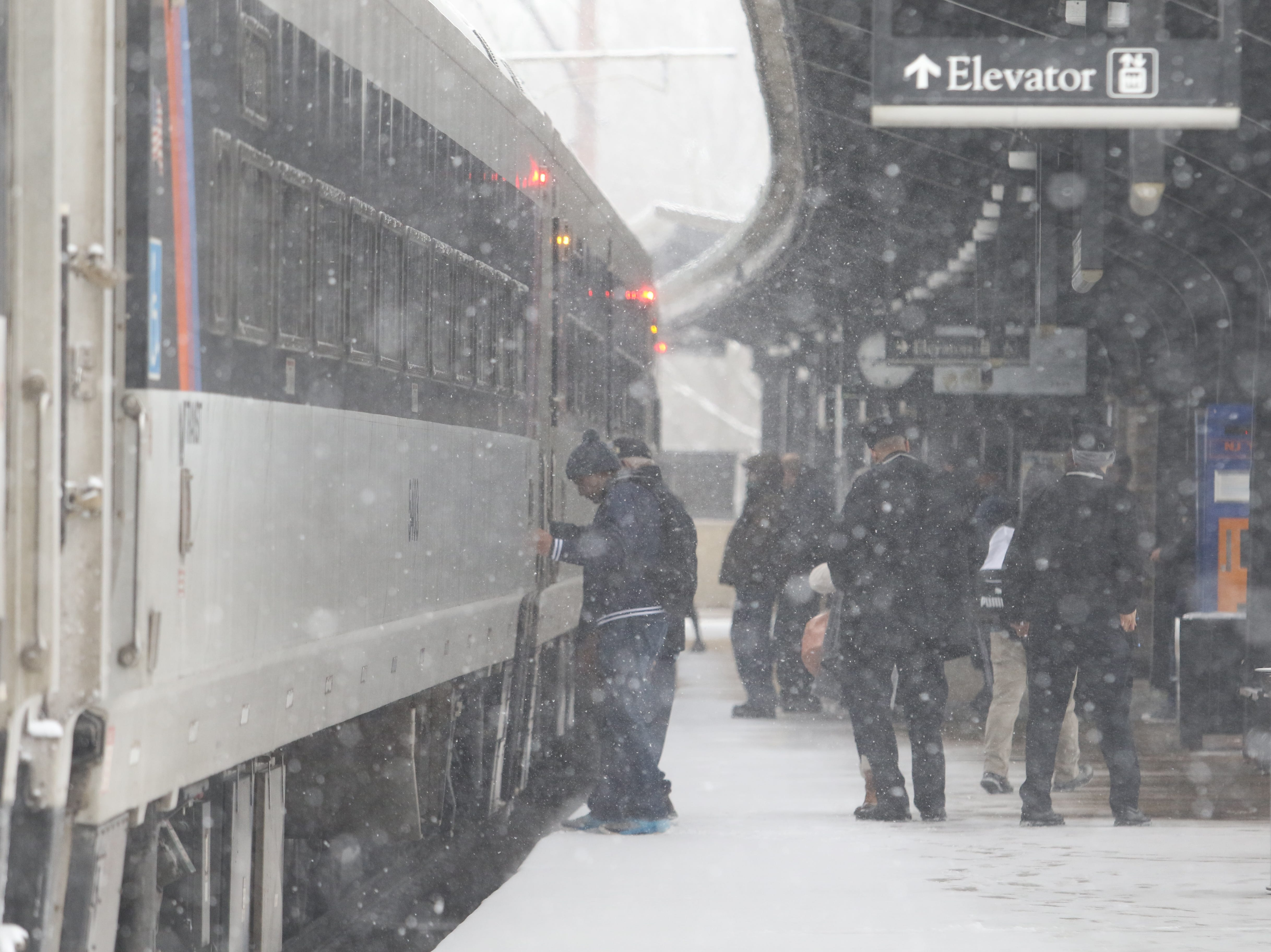 Afternoon commuters board the train that pulled into the Morristown Train Station in heavy snow this afternoon on February 20, 2018.