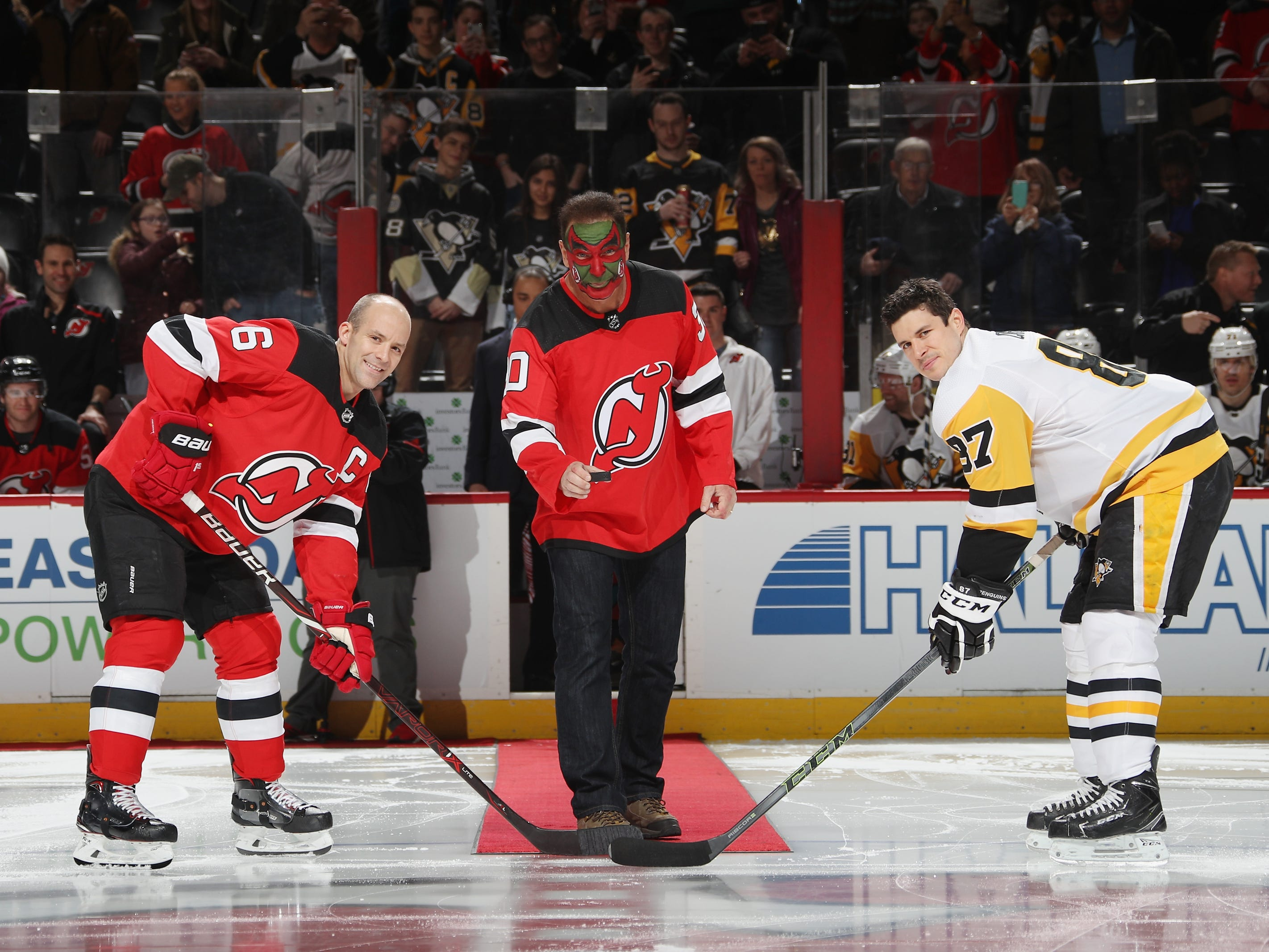"""Patrick Warburton who played the part of David Puddy on the TV show """"Seinfeld"""" drops the puck between Andy Greene #6 of the New Jersey Devils and Sidney Crosby #87 of the Pittsburgh Penguins at the Prudential Center on February 19, 2019 in Newark, New Jersey."""