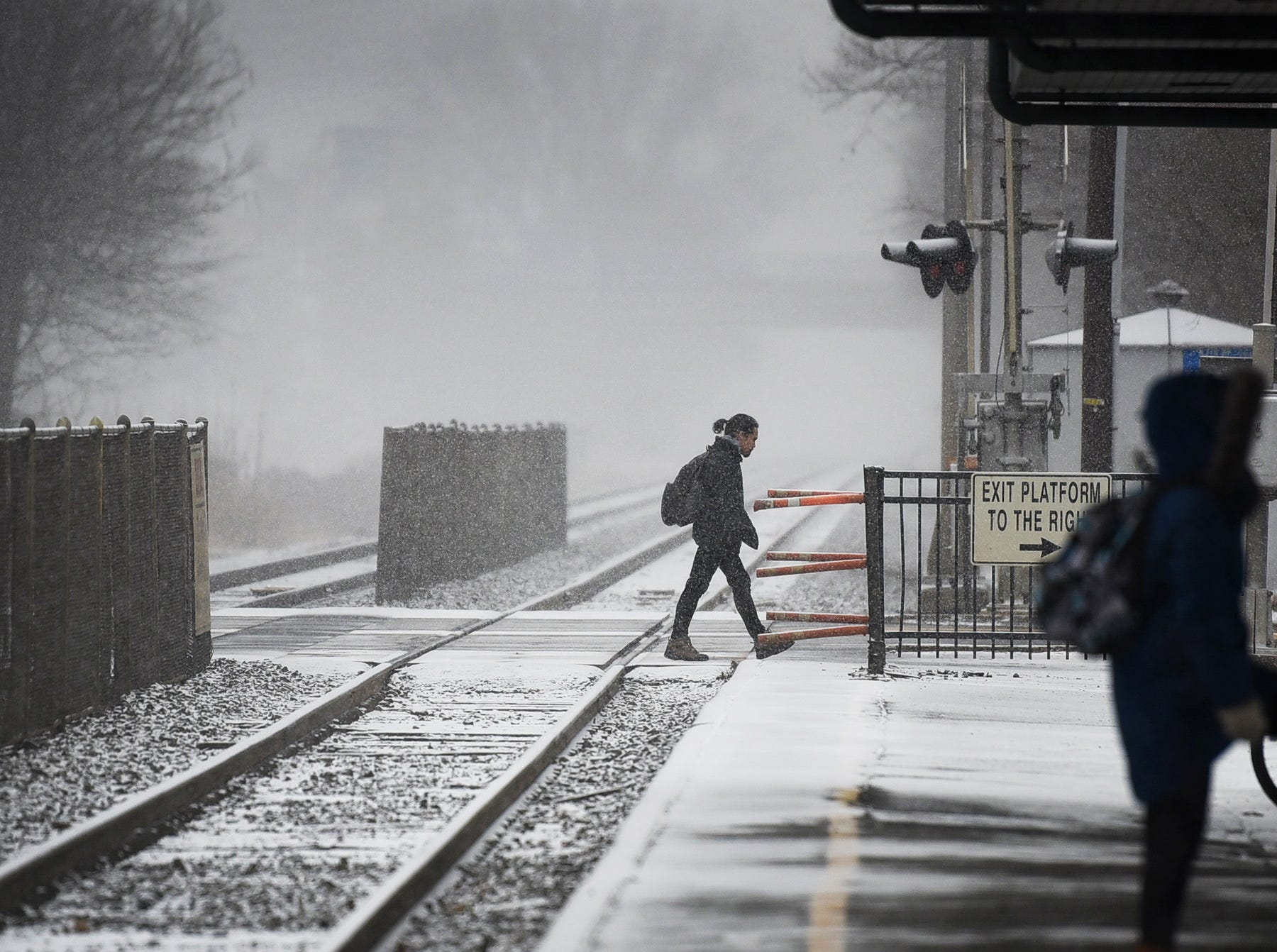 A pedestrian crosses the rail road tracks as snow begins to fall in Fair Lawn on 02/20/19.