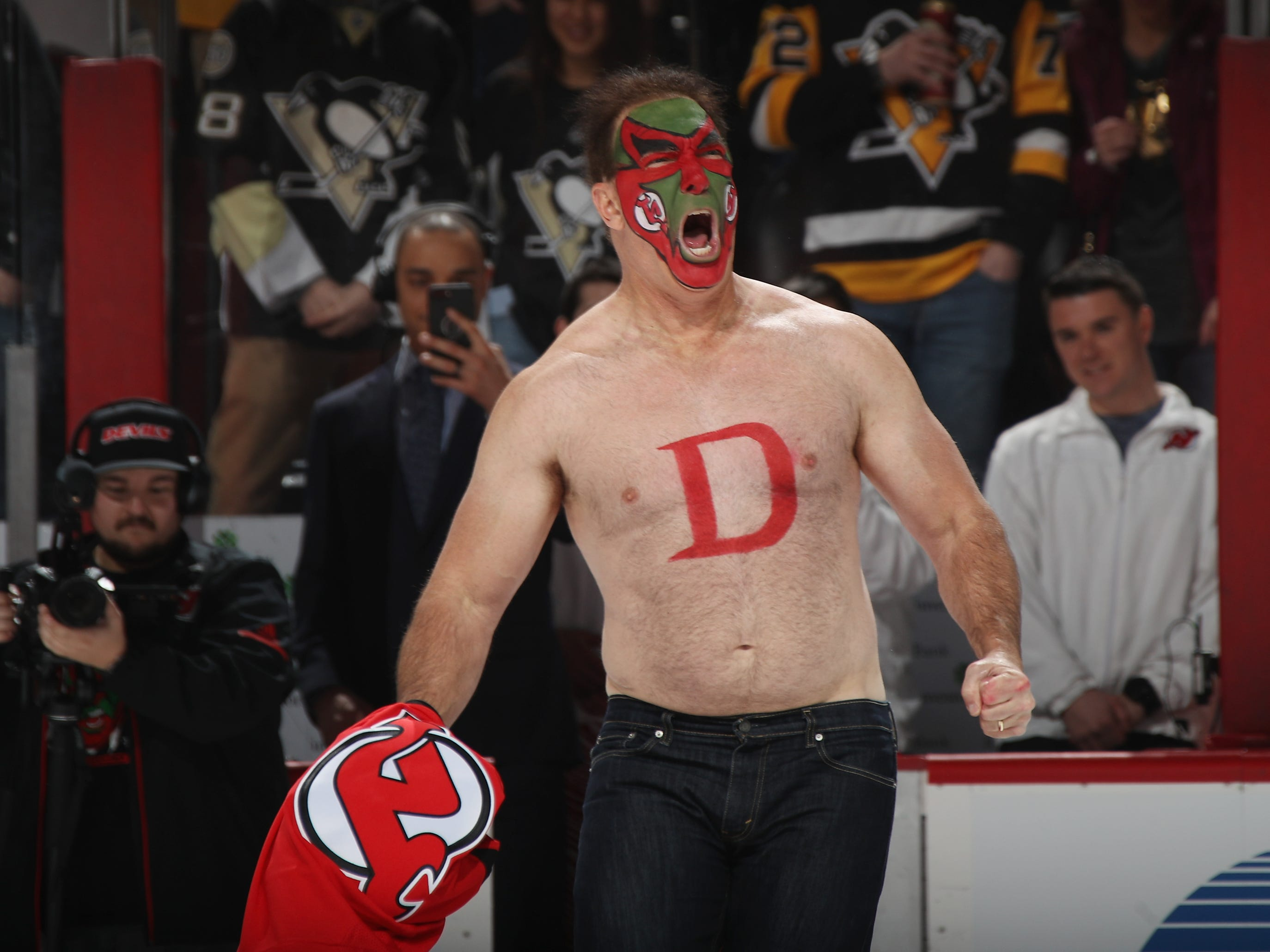 """Patrick Warburton who played the part of David Puddy on the TV show """"Seinfeld"""" walks out onto the ice to drop the puck between Andy Greene #6 of the New Jersey Devils and Sidney Crosby #87 of the Pittsburgh Penguins at the Prudential Center on February 19, 2019 in Newark, New Jersey."""