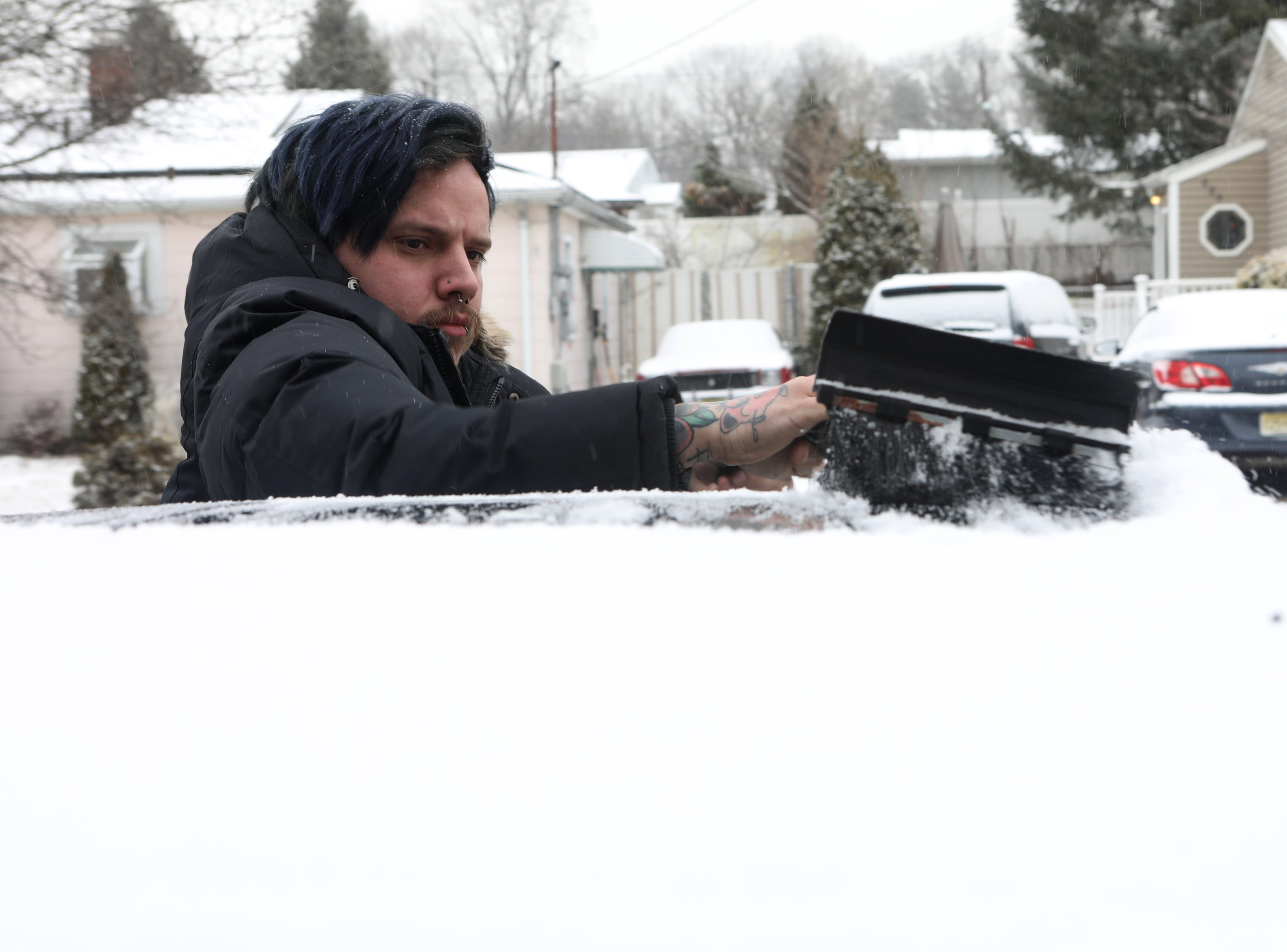 Joseph Rolan, 28, of Elmwood Park, removes snow from his car, Wednesday, February 20, 2019.