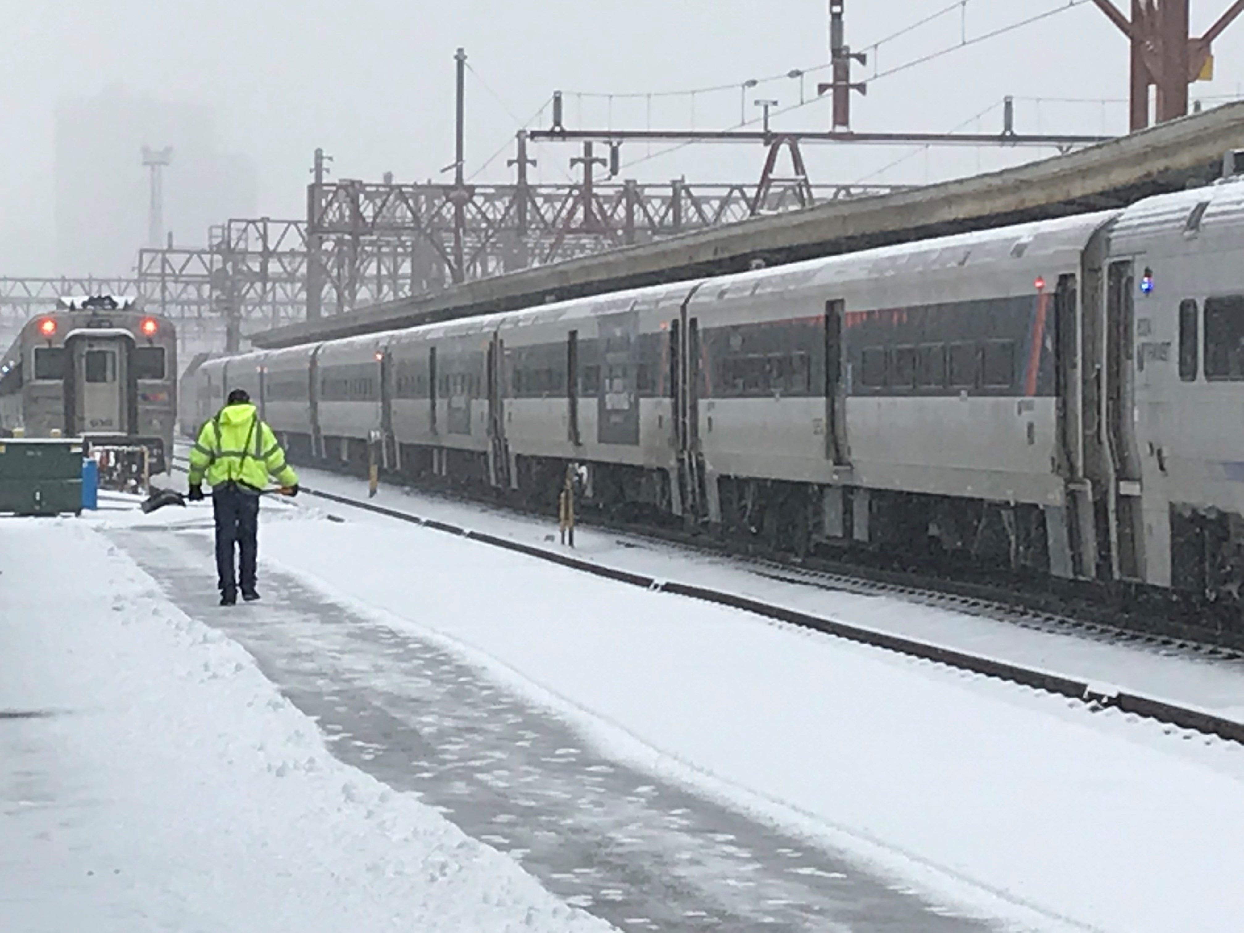A worker shovels a path to NJTransit trains at Hoboken Terminal.