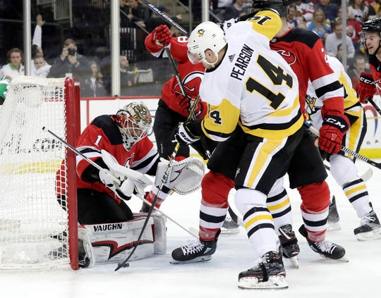 New Jersey Devils goaltender Keith Kinkaid (1) stops a shot s Pittsburgh Penguins left wing Tanner Pearson (14) attacks during the first period of an NHL hockey game, Tuesday, Feb. 19, 2019, in Newark, N.J. (AP Photo/Julio Cortez)