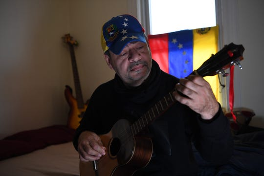 William Sanchez, 50, who arrived from Venezuela in October, plans to file for asylum to become a legal resident. Sanchez plays a cuatro at his home in Bogota on February 20, 2019.