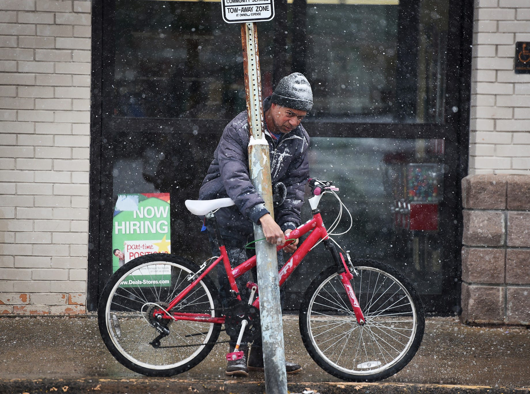 A man locks his bike as the snow falls in Fair Lawn on 02/20/19.