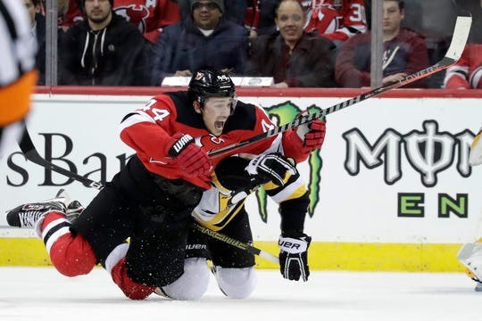 New Jersey Devils left wing Miles Wood, left, falls to the ice while competing for the puck with Pittsburgh Penguins right wing Bryan Rust during the first period of an NHL hockey game, Tuesday, Feb. 19, 2019, in Newark, N.J. (AP Photo/Julio Cortez)