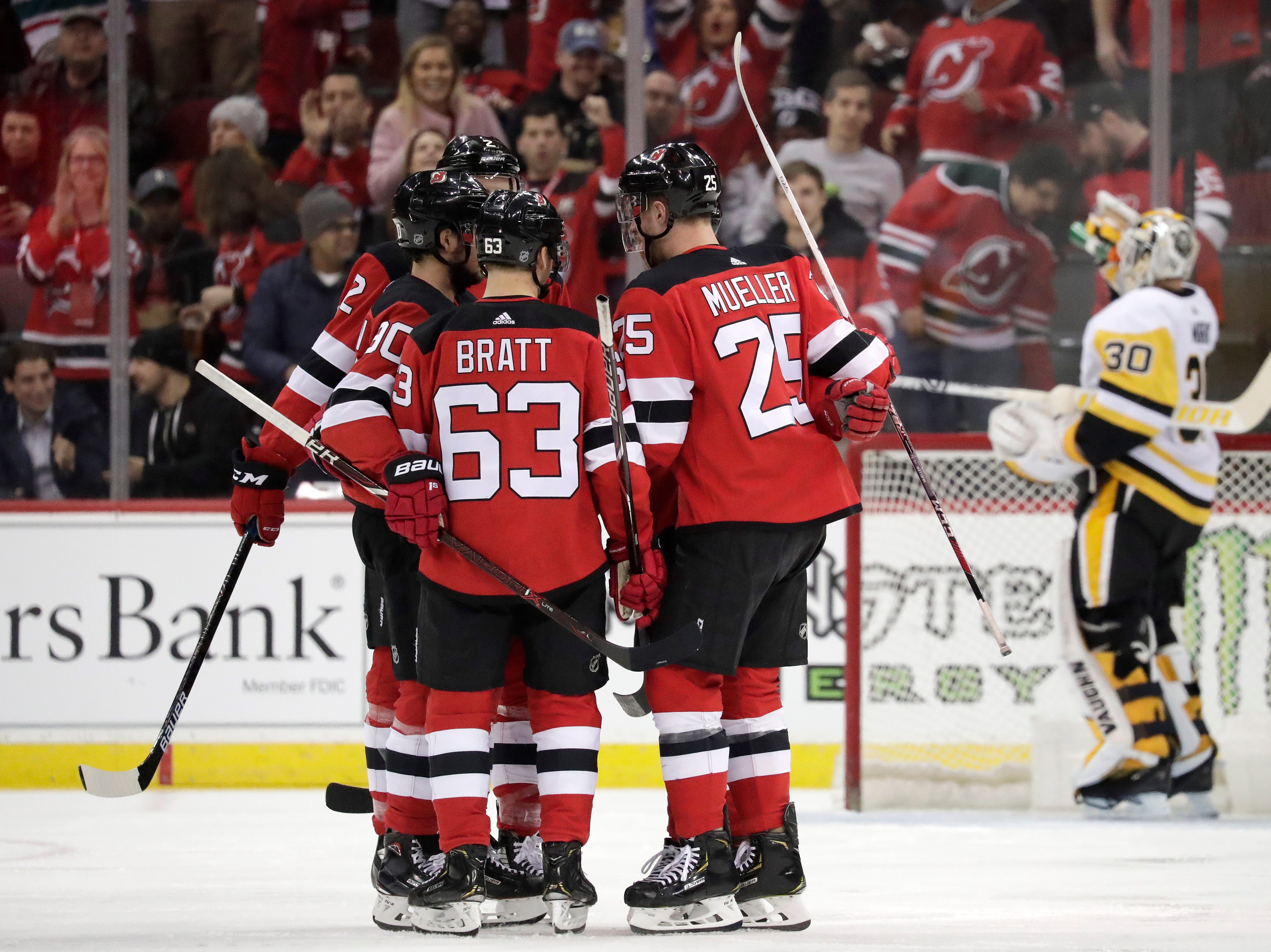 New Jersey Devils players celebrate a goal by Jesper Bratt (63), of Sweden, as Pittsburgh Penguins goaltender Matt Murray, far right, refreshes himself during the first period of an NHL hockey game, Tuesday, Feb. 19, 2019, in Newark, N.J. (AP Photo/Julio Cortez)