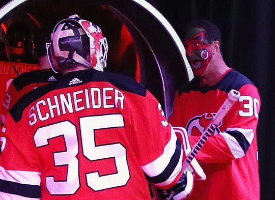 """Patrick Warburton who played the part of David Puddy on the TV show """"Seinfeld"""" greets Cory Schneider #35 of the New Jersey Devils prior to the game against the Pittsburgh Penguins at the Prudential Center on February 19, 2019 in Newark, New Jersey. The Devils gave out 'Puddy' bobble head dolls before the game."""