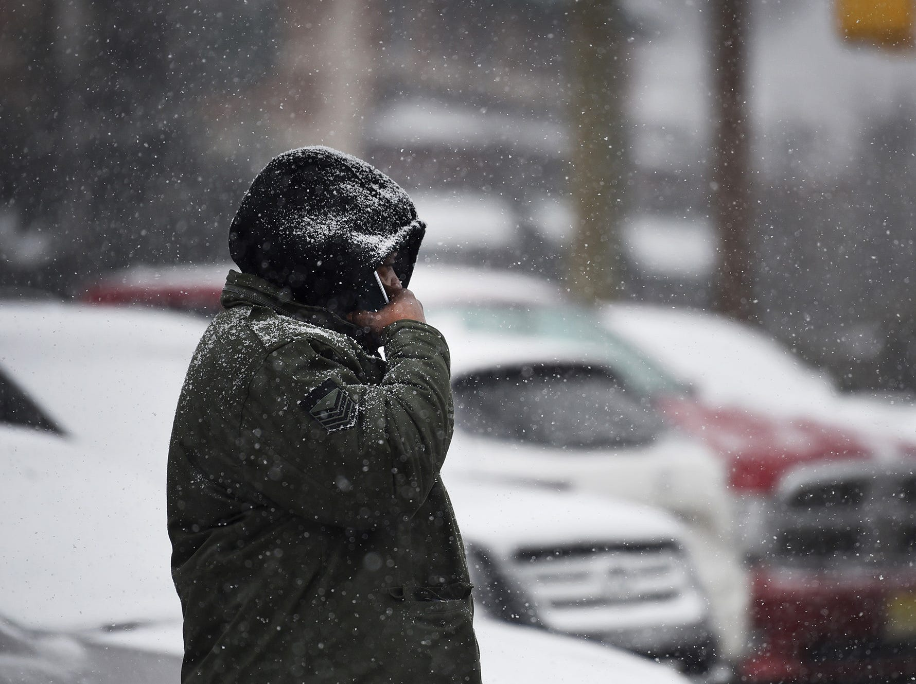 A man waits for a bus to come as the snow falls in Fair Lawn on 02/20/19.