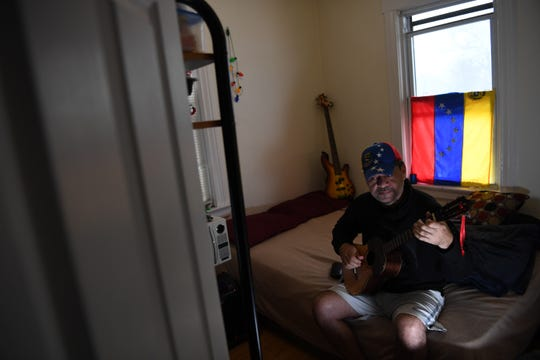 William Sanchez, 50, who arrived from Venezuela in October, plans to file for asylum to become a legal resident. Sanchez plays a cuatro as he watches television at his home in Bogota on February 20, 2019.