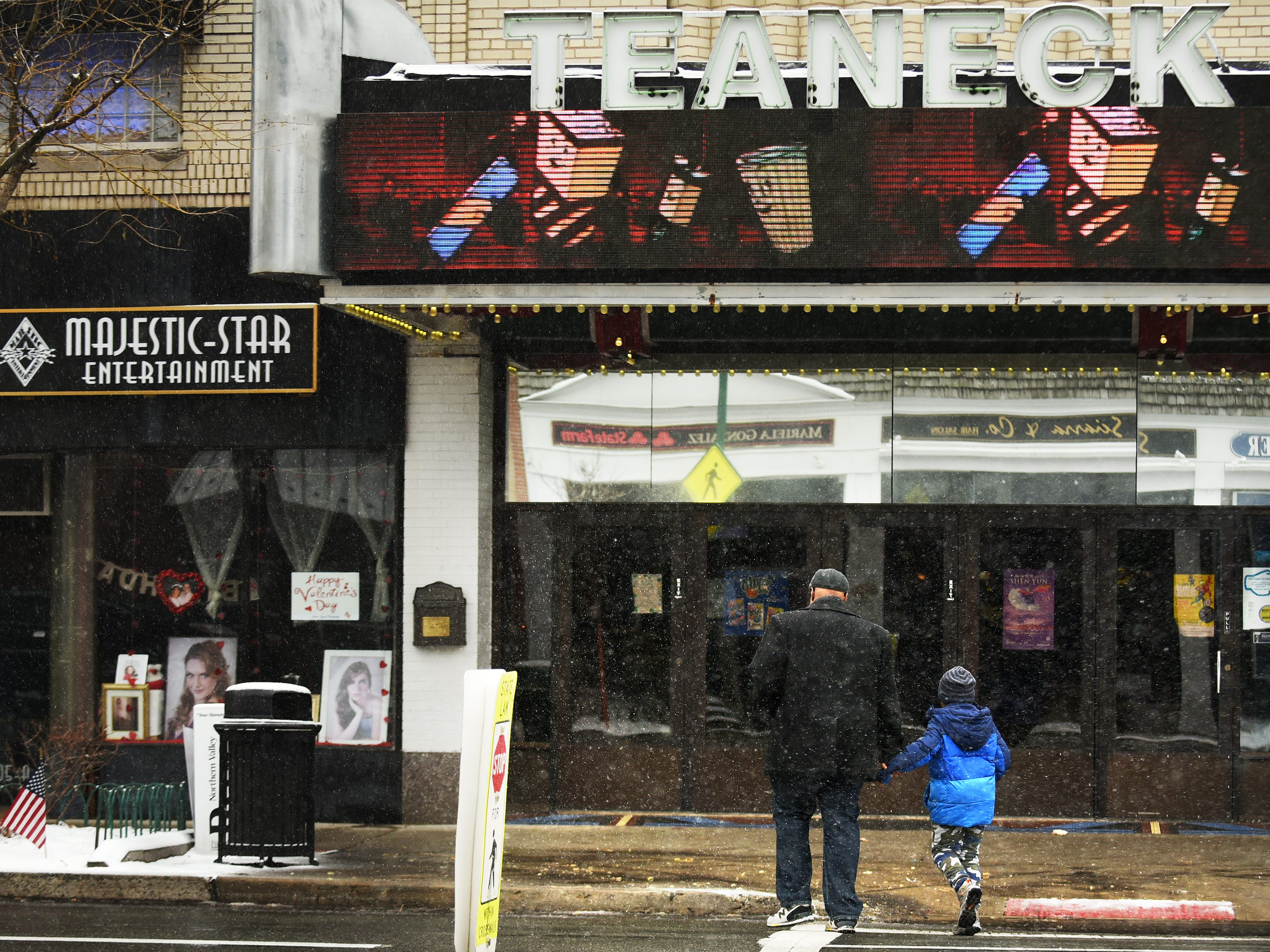 A man and child cross Cedar Lane in front of the movie theater as snow falls in Teaneck on Wednesday February 20, 2019.