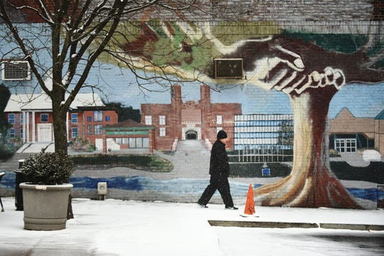 A man walks by a mural as snow falls on Cedar Lane in Teaneck on Wednesday February 20, 2019.