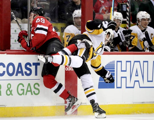 New Jersey Devils right wing Joey Anderson, left, collides with Pittsburgh Penguins center Jared McCann during the first period of an NHL hockey game, Tuesday, Feb. 19, 2019, in Newark, N.J. (AP Photo/Julio Cortez)