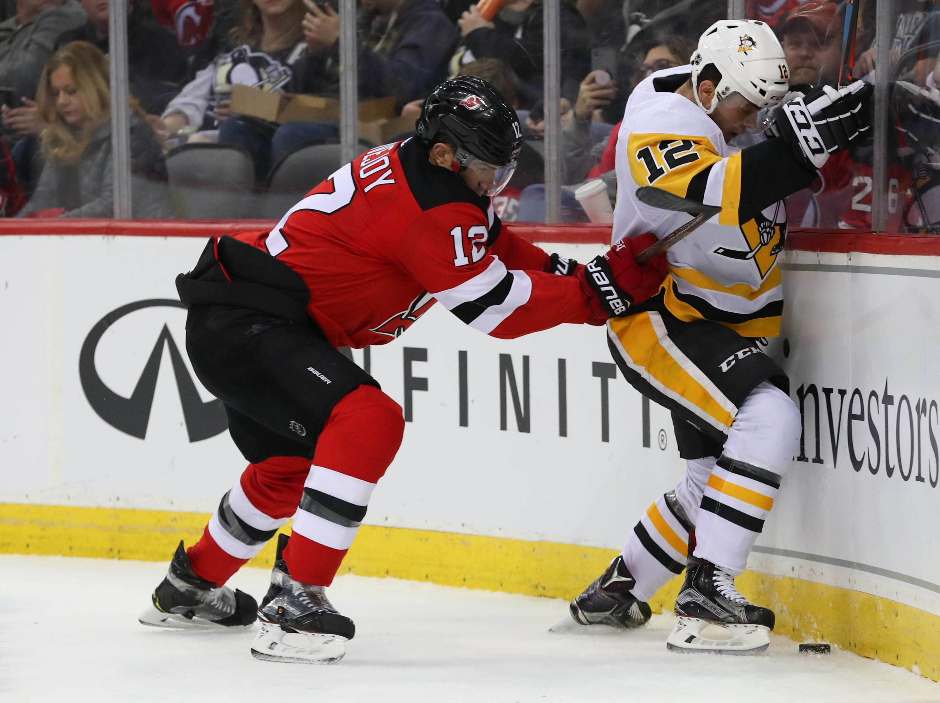 Feb 19, 2019; Newark, NJ, USA; New Jersey Devils defenseman Ben Lovejoy (12) hits Pittsburgh Penguins center Dominik Simon (12) during the first period at Prudential Center. Mandatory Credit: Ed Mulholland-USA TODAY Sports