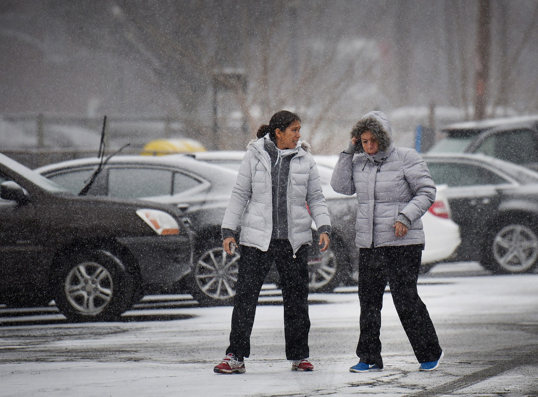 Two women walk through a parking lot as the snow falls in Fair Lawn on 02/20/19.