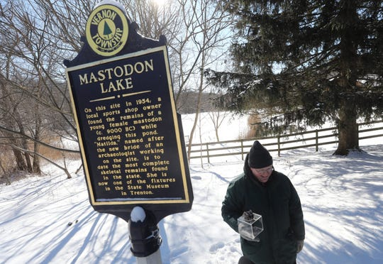 New Jersey State Geologist, Jeffrey Hoffman holding a mastodon tooth by Mastodon Lake in Vernon on January 31, 2019, telling the story of a mastodon skeleton that was found in the lake in 1954. It is part of a statewide report on the history of NJ mastodons.