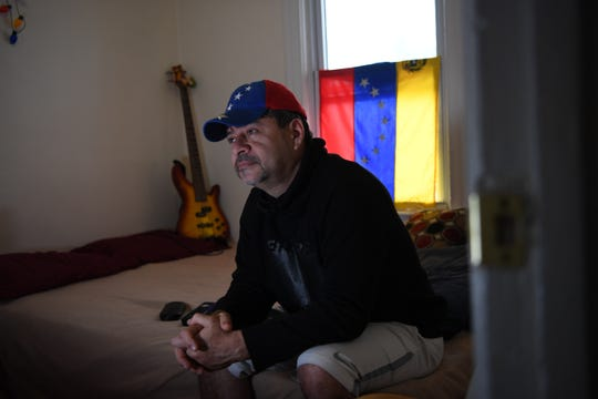 William Sanchez, 50, who arrived from Venezuela in October, plans to file for asylum to become a legal resident. Sanchez watches television at his home in Bogota on February 20, 2019.