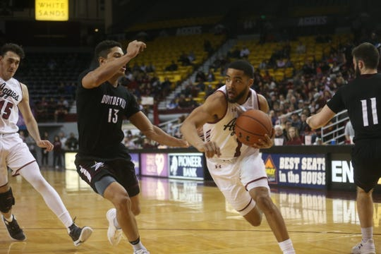 Aggies' Shunn Buchanan drives to the basket past Texas A&M International's Xabier Gomez during the second half of the non-conference game Feb. 20 game.