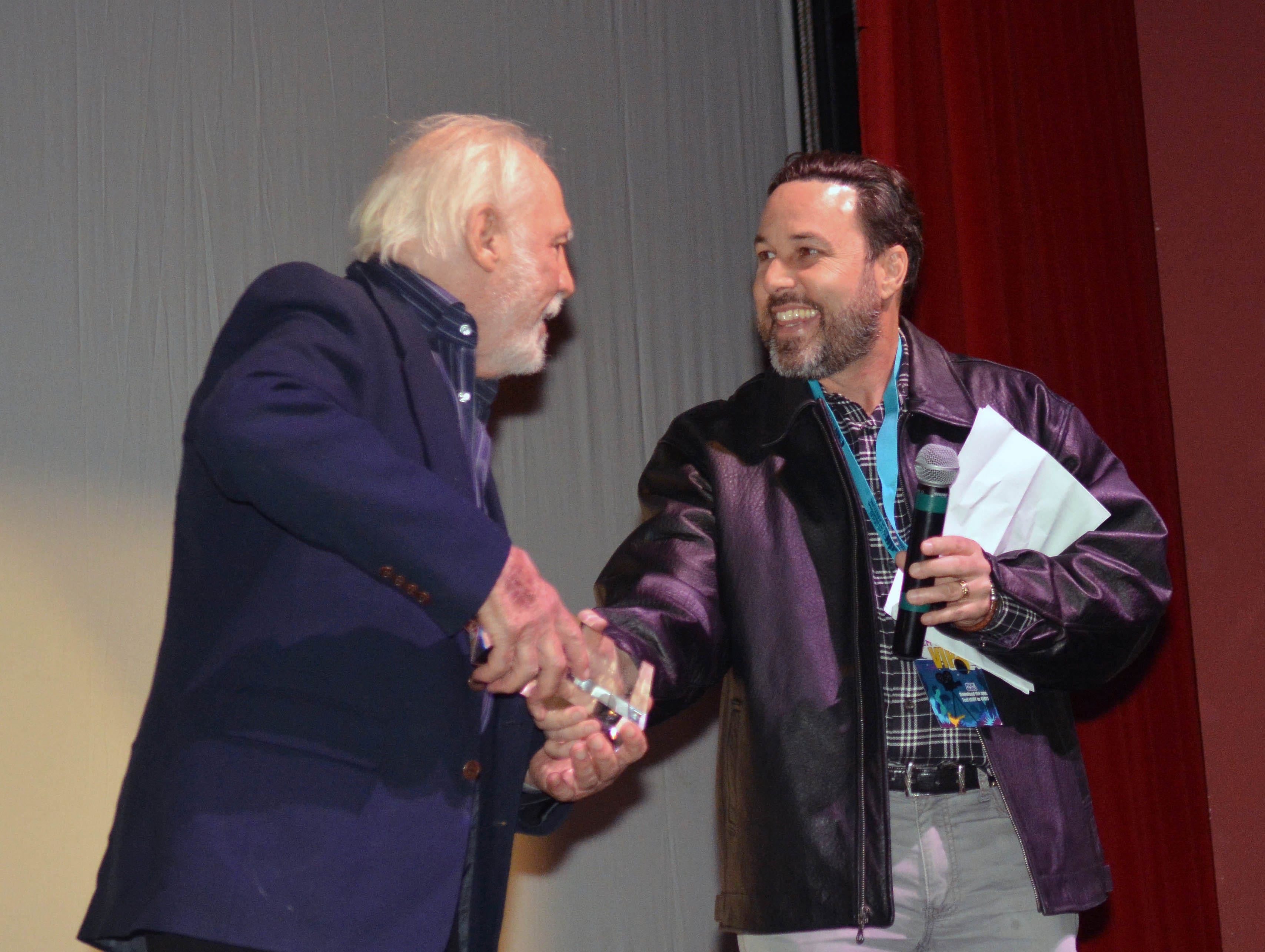 """Robert M. Young, left, receives the LCIFF Auteur Award from Las Cruces International Film Festival Director Ross Marks on Tuesday at the Rio Grande Theatre, following a screening of Young's """"The Ballad of Gregorio Cortez."""""""