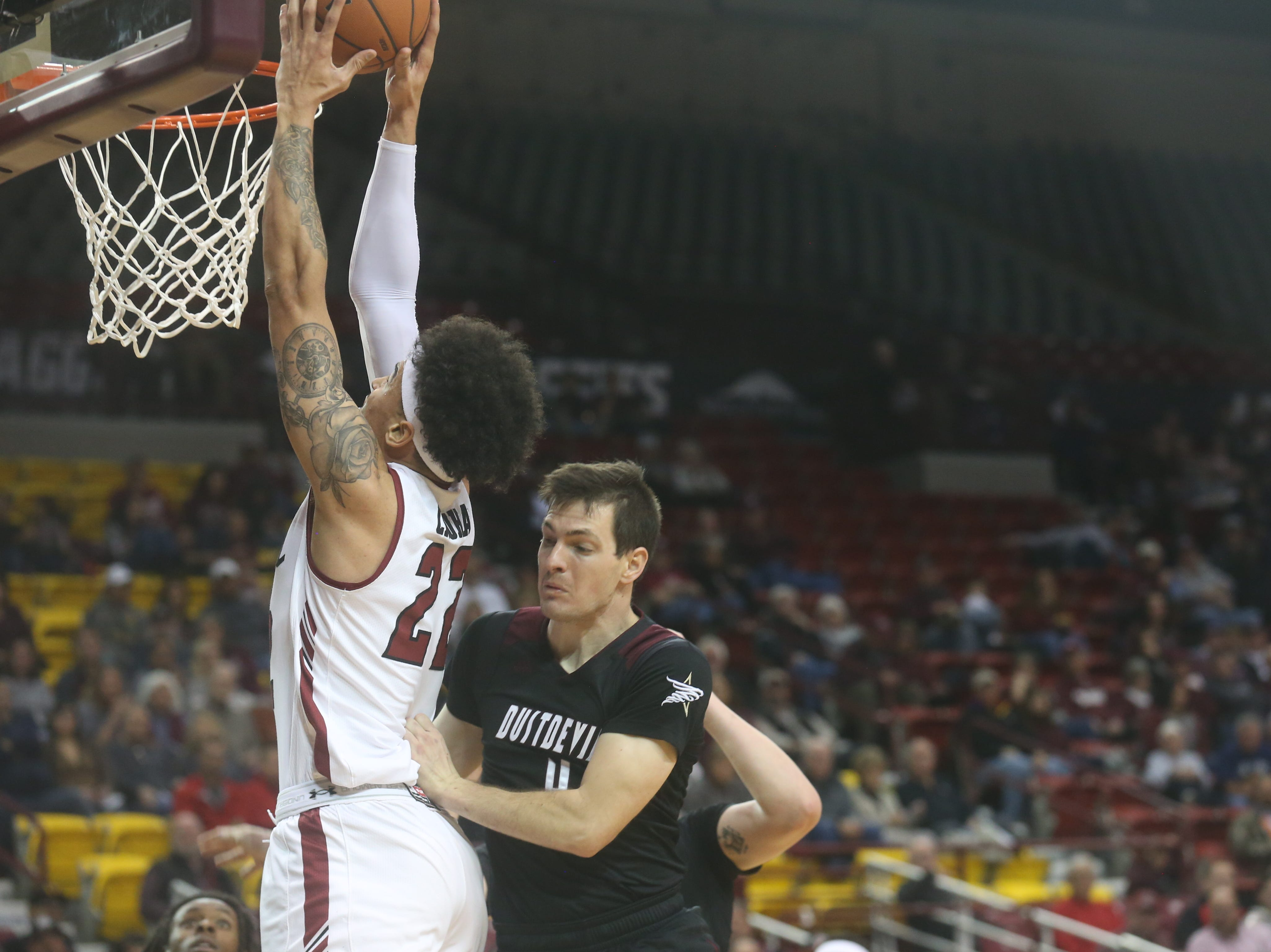 Aggies' Eli Chuha scores a power dunk as Texas A&M International's Danny Spinuzza  moves to slowly to stop the score.