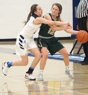 Livonia Spartan Kerry Donhue, left, tips the ball out of the hands of Howell Highlander Allison Pennala.