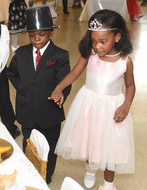Being the perfect gentleman, this Southwest Elementary Pre-K student escorts his date to her seat as they celebrate Valentnes Day at the school's annual Tiaras and Top Hats luncheon.