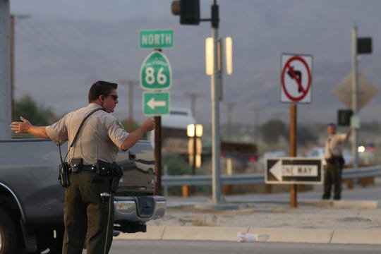 Law enforcement officials direct traffic near Highway 86 S and Dillon Road, where shots were reportedly fired and a carjacking occurred about 4:45 p.m. on Thursday, April 10, 2014.