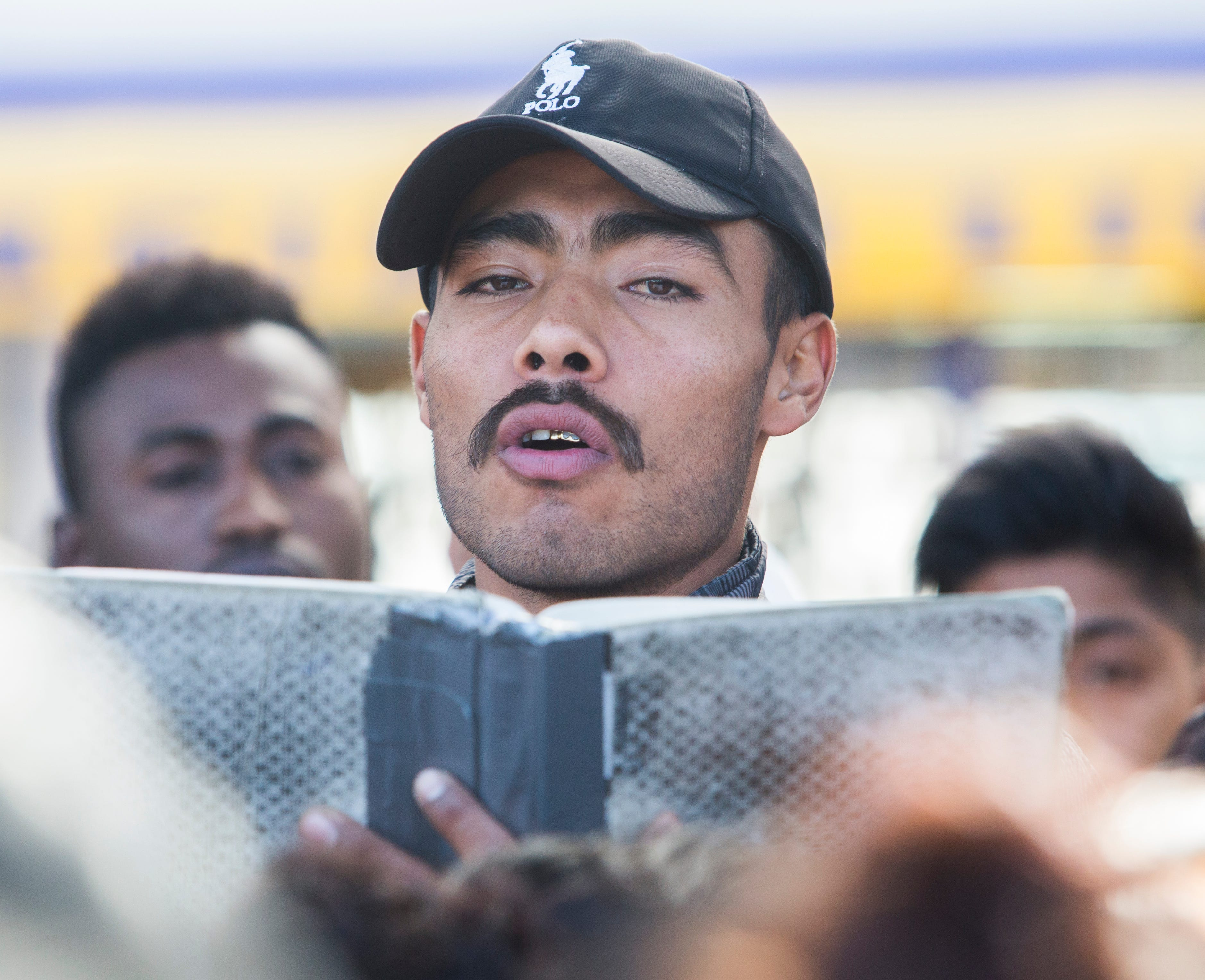 In November 2018, Yovani, a migrant from Michoacán, reads aloud the names of asylum seekers who will be interviewed by U.S. Customs and Border Protection officials in Tijuana that day.