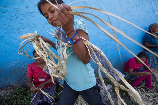 A child carries thin strips of dried palm leaves, which they sell at craft markets. Buyers weave them into hats and baskets.