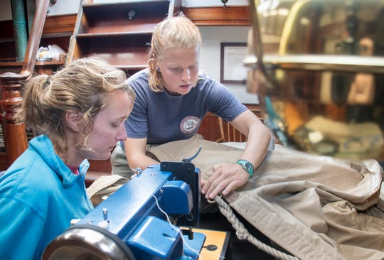 At right, Angela Wilt, chief mate on the Lynx, teaches Sara VanderLeest, boatswain and deckhand on the Lettie G. Howard, how to use a sewing machine to fix an awning on board the Lynx on Wednesday. Crews from both ships, which are currently docked in Pensacola, are taking advantage of the inclement weather to complete ship repairs.