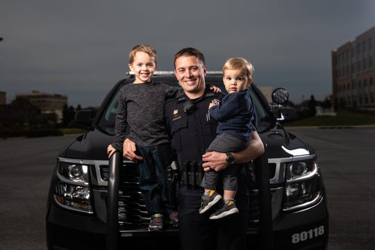 Pensacola police officer Stephen Grogan holds his sons Tristan, left, and Camden, right.